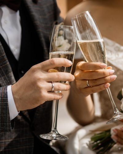 Front view of wedding couple's hands with champagne glasses and wedding bouquet